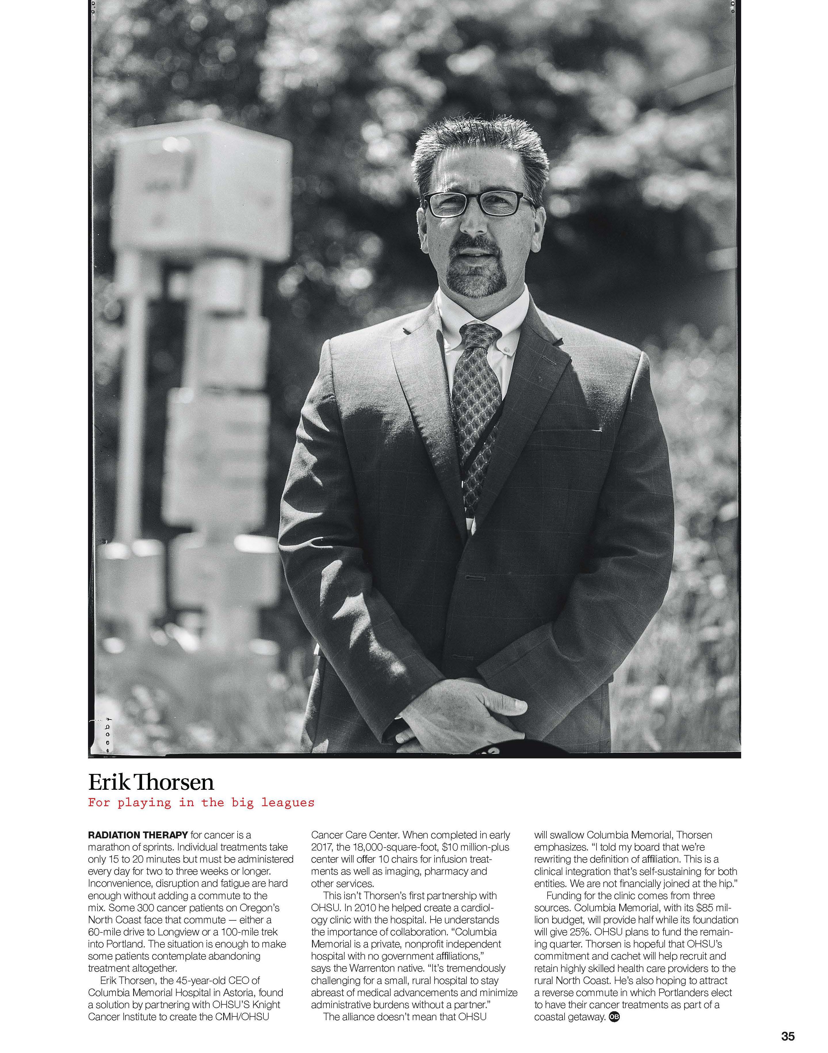 Erick Thorsen stands outdoors in suit in environmental portrait