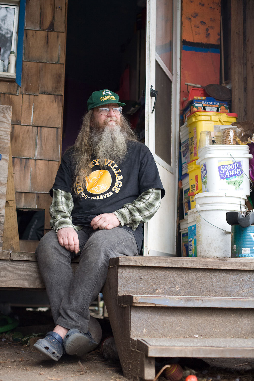 Tim McCarthy, former chairperson of Dignity Village sits on porch