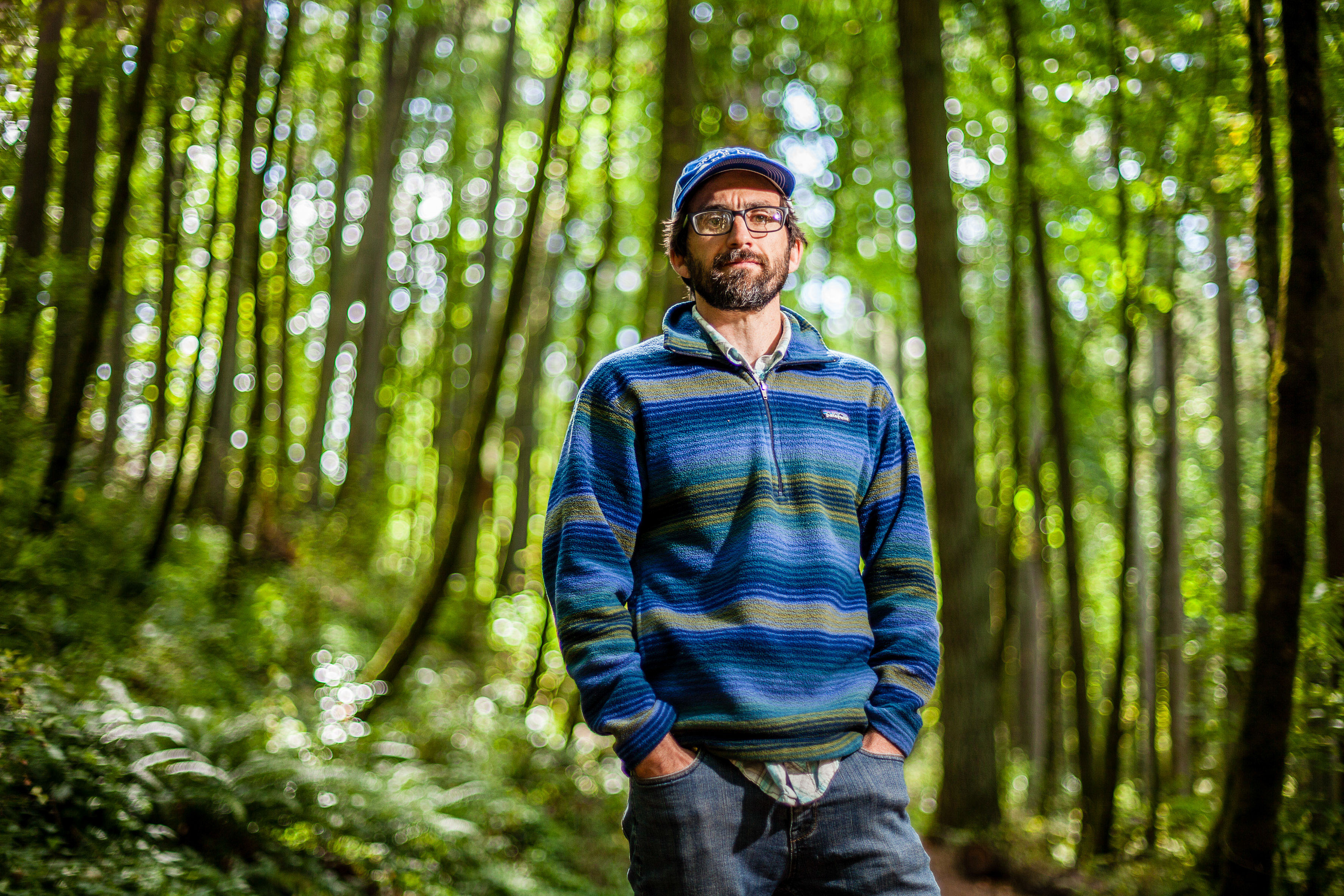 Portrait of Eugene Conservationist standing in forest with blue hat