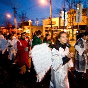 Procession of children wearing angel wings walk down street during St. Johns Posada