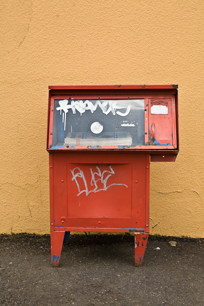 red newspaper box against yellow wall