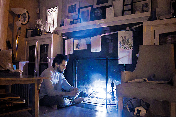 Man sits by fireplace