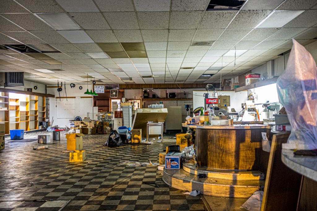 An empty restaurant building shot through the window.  The light is dim and moody.  The room is litter with debris.