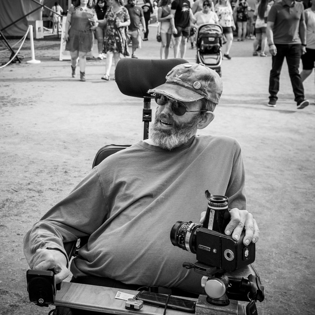 Ward Shortridge, black and white image of a bearded man with a cap in his wheelchair with a mounted Hasselblad camera in front of him.