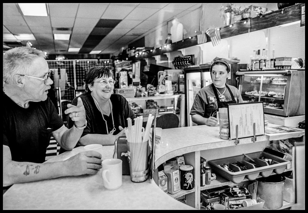 Three people sitting at a counter.  Left to right is a man in is 60's with glasses.  A middle-aged woman smiling (this is Pattie) and a young woman dressed as a waitress.