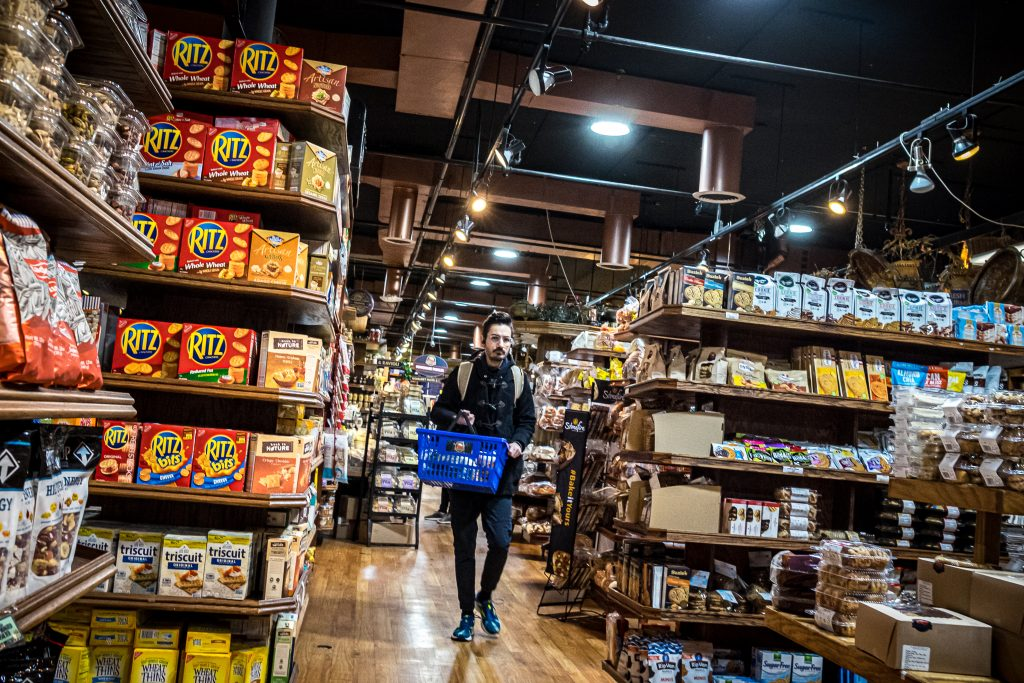 young man dressed in black, holding a blue shopping basket walking towards the camera in a grocery store.  To the left is a shelf of Ritz crackers.